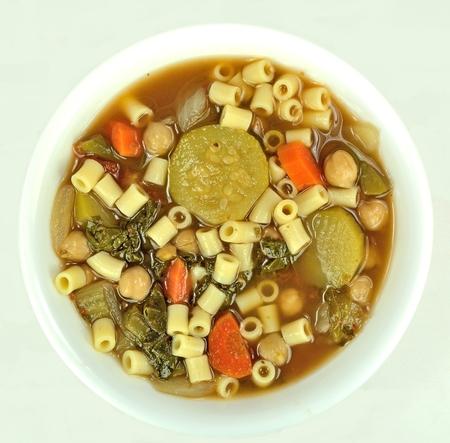 White bowl of minestrone soup on a light background. Фото со стока