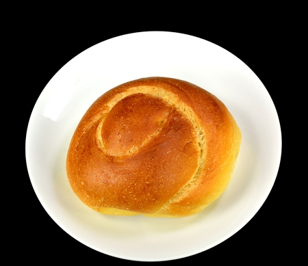 Egg twist roll on a white plate on a black background.