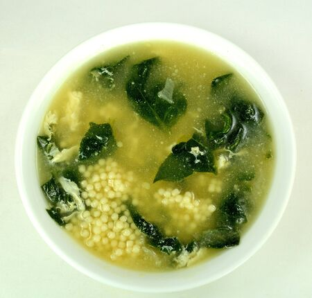 to pepe: Spinach egg drop soup with acini di pepe on a white background. Stock Photo