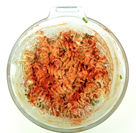 Macaroni salad in a glass bowl on a white background.