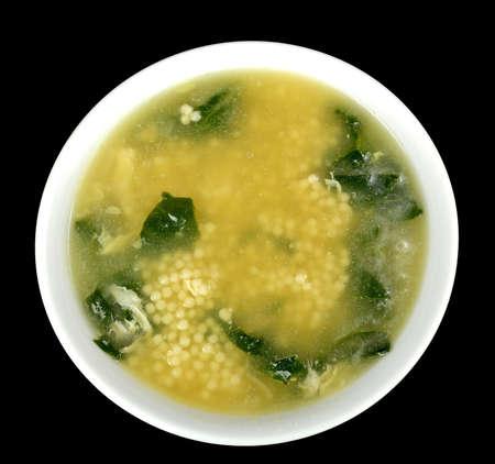 stracciatella: Spinach egg drop soup with acini di pepe on a black background.