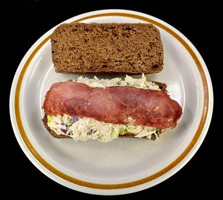 pumpernickel: Chicken salad and bacon sandwich on pumpernickel roll. Stock Photo