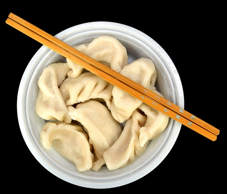 Steamed vegetable dumplings with chop sticks on a black background. Stock Photo