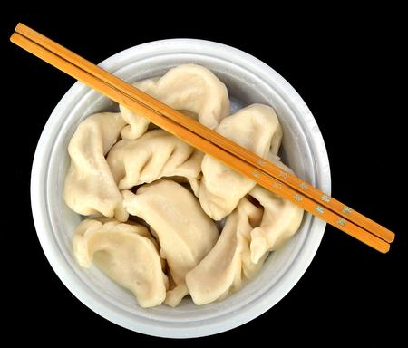 chop sticks: Steamed vegetable dumplings with chop sticks on a black background. Stock Photo