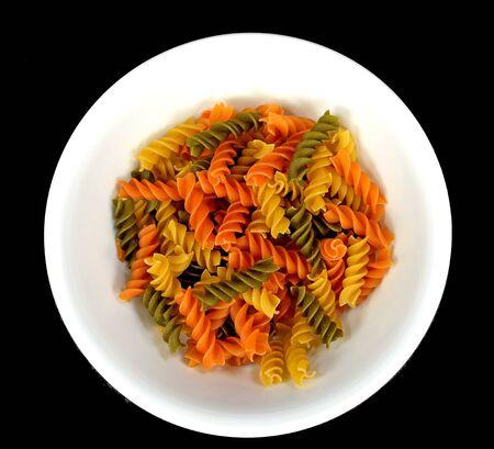 tri  color: Tri color rotelli pasta in a white bowl on a black background.