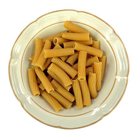 白い背景のリガトーニ全粒小麦パスタのボウル。