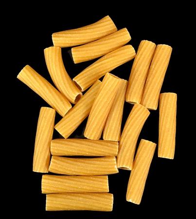 黒の背景にリガトーニ全粒小麦パスタ。 写真素材