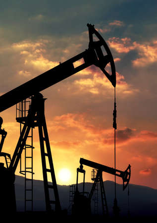 oil pump jack against sunset Stock Photo