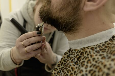 a man with a beard sits in a barbershop chair. a man shaves his beard. a man shaves the beard of a female hairdresser. trimmer and comb. man shorn and shears a beard in the salon Stok Fotoğraf