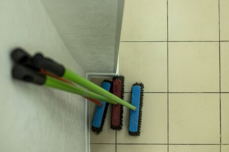 mops of different colors stand near the wall in a clean room. brushes for sweeping the floor stand near the wall. three brushes for the floor. clean indoors. There is no dirt in the building.