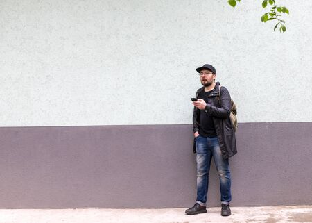 a man of Central Asian appearance is standing near the wall with a phone in his hands. he is confused, surprised and did not expect what happened next to him. two-color background