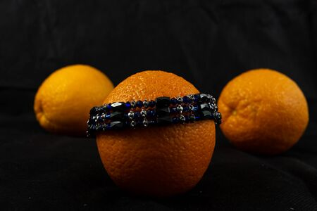 bracelet with unprecious greenish-hued stones similar to emeralds. three oranges are tonally in harmony with the bracelet. jewelry on the hand for a woman. jewelry for women and girls