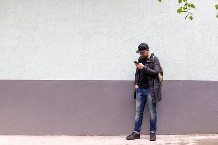 a good-looking man in a black raincoat, cap, and glasses. A man stands against a two-color wall and looks intently at his phone. very style Stok Fotoğraf