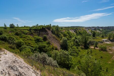 A beautiful summer landscape overlooking an old abandoned quarry and a race track deep in an abandoned quarry. Blue skies and clouds, trees and lots of greenery everywhere. High quality photo