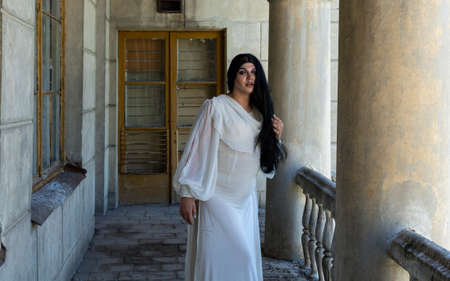 Drag queen posing close to old building in white dress. A wig with Black long hair and make up. High quality photo