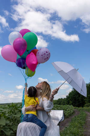 A woman in a white loose dress and little girl, who sitting on a knees of a woman with blond hair holds a whole bunch of balloons. The boundless blue sky and clouds. High quality photo