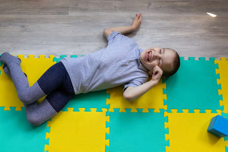 Boy with cerebral palsy in the conditions of his apartment. He reacts vividly to everything that happens around him and shows it with his personality. High quality photo