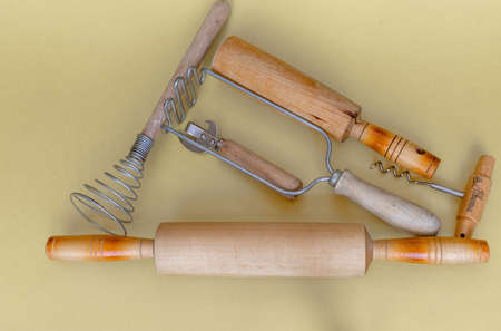 Items of kitchen utensils: a rolling pin, press for mashed potatoes, egg beater, bottle opener. All items are made partly of wood and metal. High quality photo