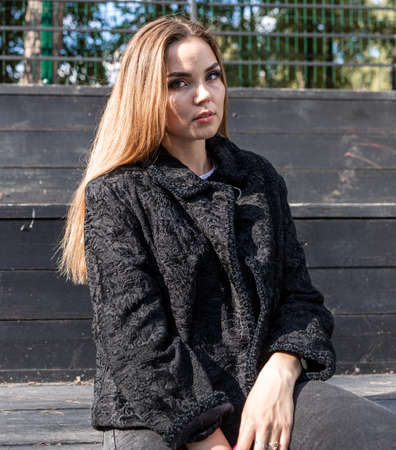 a beautiful girl with long hair and expressive eyes poses in a fur coat in a Park. High quality photo Archivio Fotografico