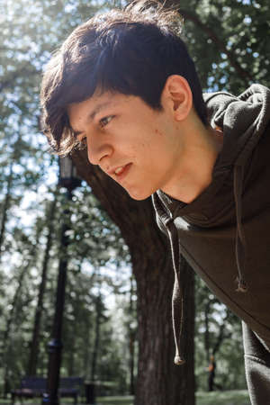a young guy of Eastern appearance with black hair and a handsome expressive face poses in a Park against the background of trees and architecture. High quality photo