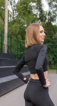A Woman makes an elegant pose. Beautiful woman in sport tiny costume standing over park sport ground. Portrait of. High quality photo Standard-Bild