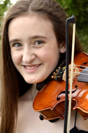 Portrait of teen girl smiling with violin photo