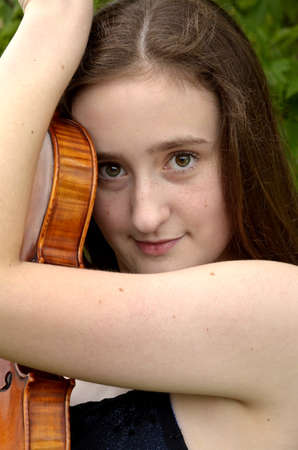 spaghetti strap: Portrait of teen girl embracing violin outside with bare shoulder Stock Photo