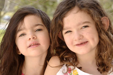 curls: Outdoor spring portrait of two young girls from the shoulders up