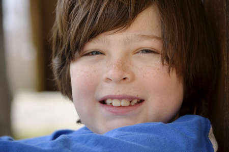 Close portrait of a young boy with freckles and blue shirt Banco de Imagens
