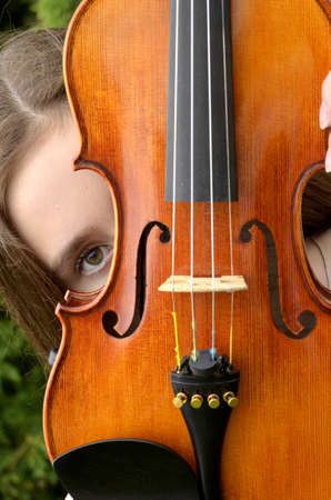 Young woman peeking around upright violin