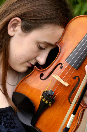 Profile portrait of teen girl holding violin tenderly