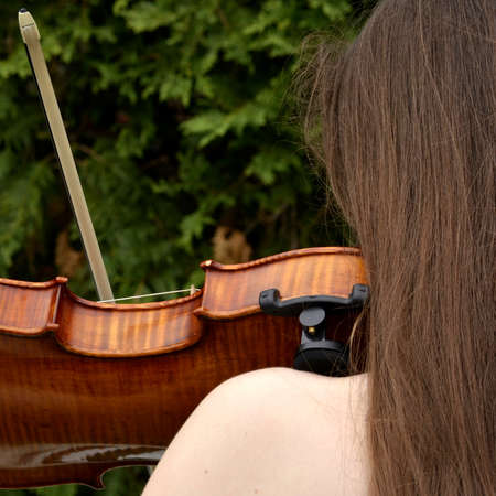 spaghetti strap: Teen girl playing violin seen from benind with long hair and bare shoulder Stock Photo