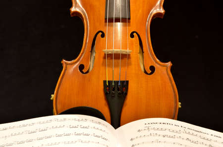 violins: Detail of upright violin with open sheet music at bottom of horizontal frame