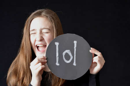 Teenaged girl laughing with eyes shut holding a round sign with chalk letters lol wearing black shirt on black background