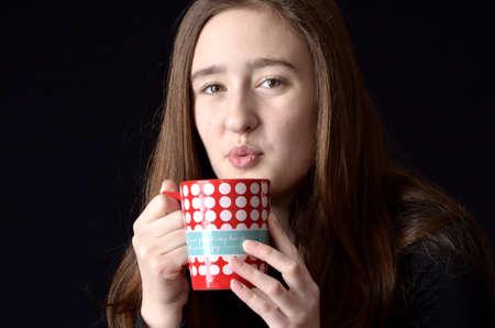 polka dotted: Chica adolescente soplando sobre polka rojo y blanco salpicado de taza usando la camisa negro sobre fondo negro