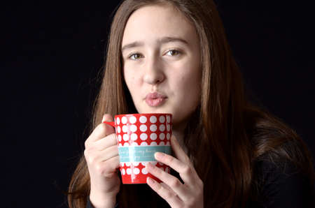 Teenaged girl blowing on red and white polka dotted coffee mug wearing black shirt on black background photo