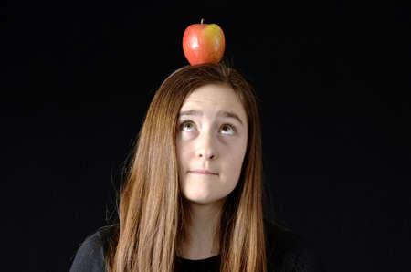 Teenaged girl looking up at apple on her head wearing black shirt on black background photo