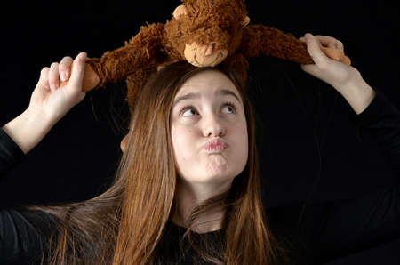 puckered: Teenaged girl holding stuffed monkey over her head looking up at it with a silly expression wearing black shirt on black background