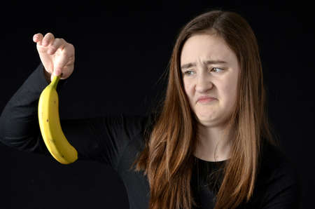 repulsive: Teenaged girl holding up a banana with a disgusted expression on her face wearing black clothing on black background