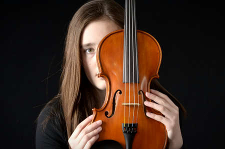 teenaged: Teenaged girl holding violin so that it hides part of her face wearing black shirt on black background Stock Photo