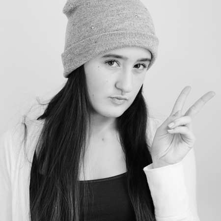 pouty: Teenaged girl wearing beanie with pouty lips holding up peace sign  Square crop in black and white  Stock Photo