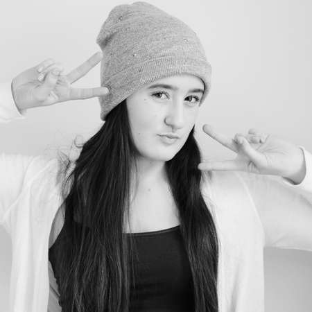 pouty: Teenaged girl wearing beanie with pouty lips holding up double peace sign  Square crop in black and white