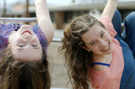 teenaged girls: Close portrait of two teenaged girls hanging from monkey bars on school playground