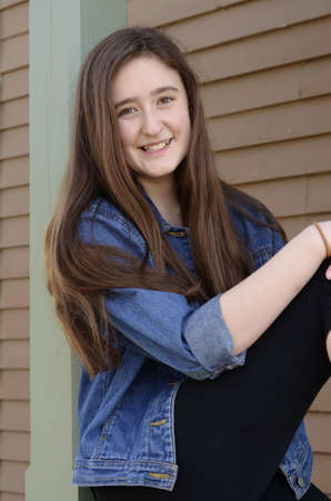 hazel eyes: Pretty teenaged girl smiling with long brown hair and hazel eyes sitting with knee up on porch railing wearing blue denim jacket