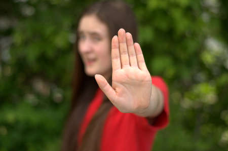Teen girl with outstretched hand wearing red shirt on green background with only the hand in focus.
