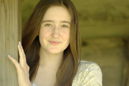hazel eyes: Head and shoulders of pretty teenaged girl with long brown hair and hazel eyes smiling with mouth closed with rustic wooden porch background Stock Photo
