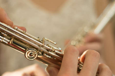 conservatory: Detail of female fingers on flute keys with copy space and soft pastel background