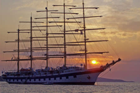 The largest sailing ship in the world, the Royal Clipper with the sun setting behind her, at anchor in Hvar, Croatia. photo