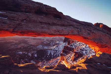 Mesa Arch glowing at sunrise in Arches National Park, Utah.