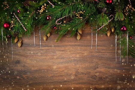 Christmas background with fir tree and decorations on wooden board. New Year or Christmas holidays concept. Copy space, top view.